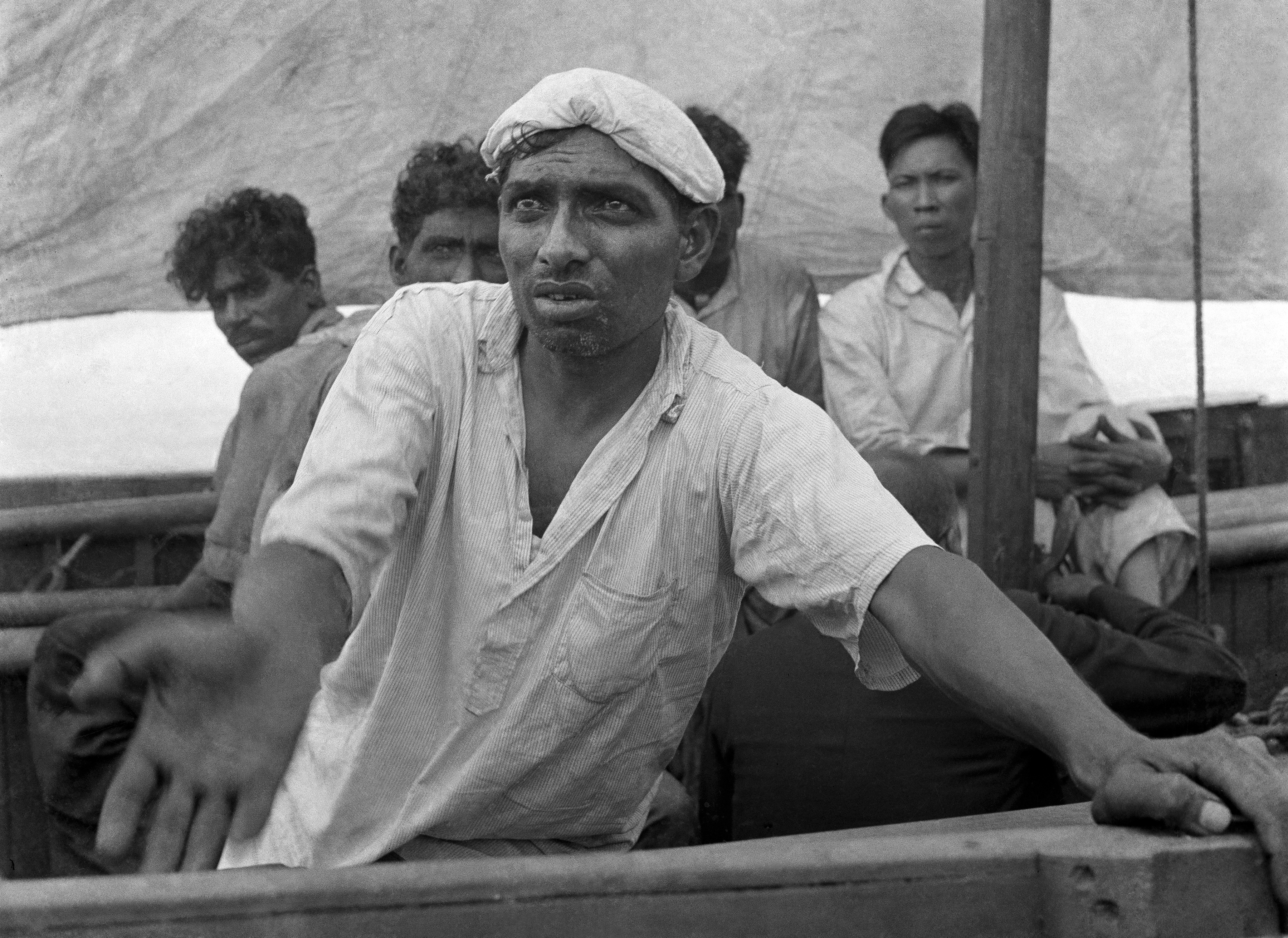 "An Indian sailor pleads for water from a lifeboat adrift on the Indian Ocean in January 1942. AP photographer Frank ""Pappy"" Noel shot this photo from his own lifeboat after a Japanese torpedo sank a ship carrying Noel and others from Singapore. Noel and his fellow survivors eventually reached Sumatra. (AP Photo/Frank Noel)"