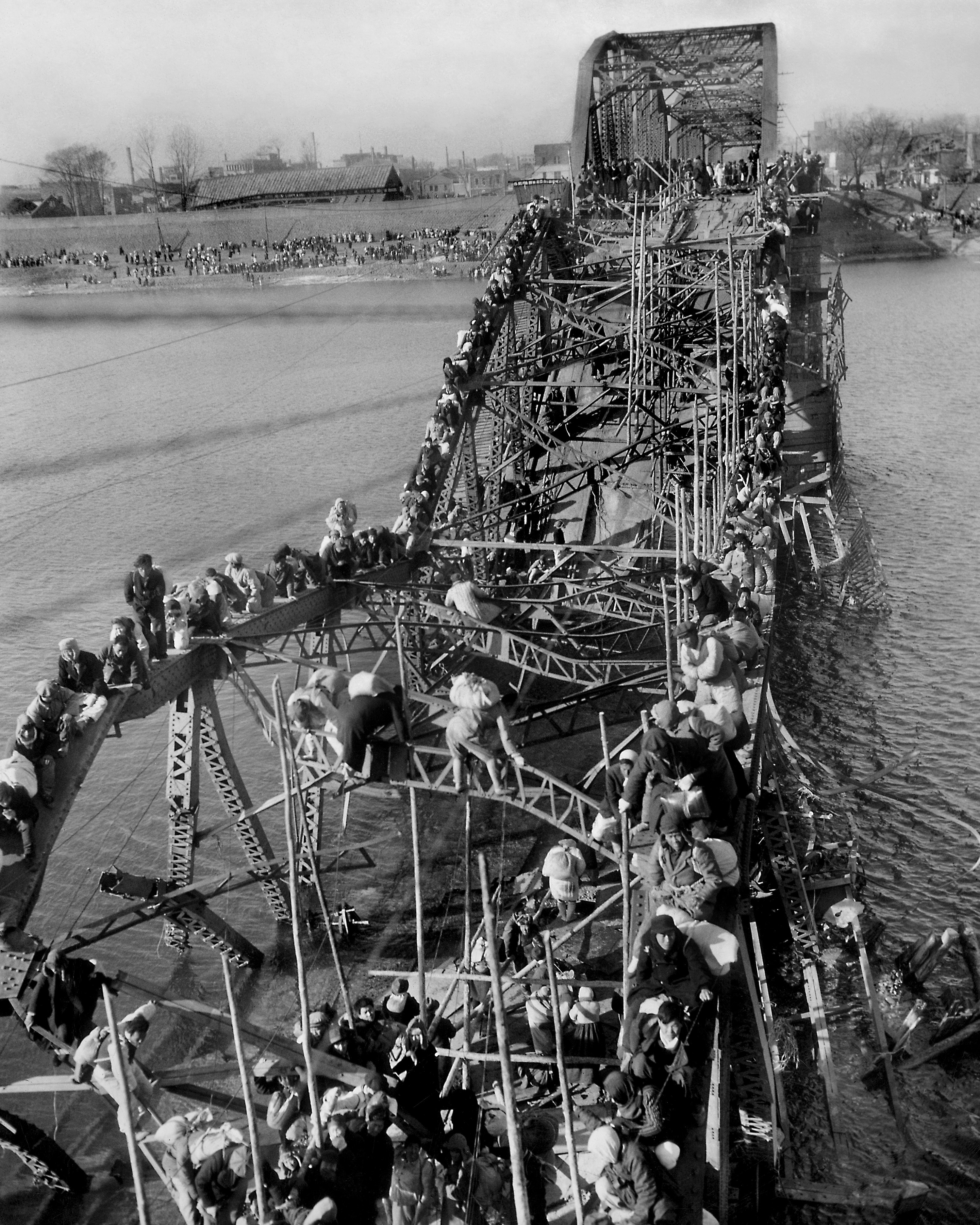 In bitter cold, residents from Pyongyang, North Korea, and refugees of other areas crawl over precarious, tangled girders of a bridge across the Taedong River on Dec. 4, 1950, as they flee south ahead of advancing Chinese Communist troops fighting on the side of North Korea. (AP Photo/Max Desfor)