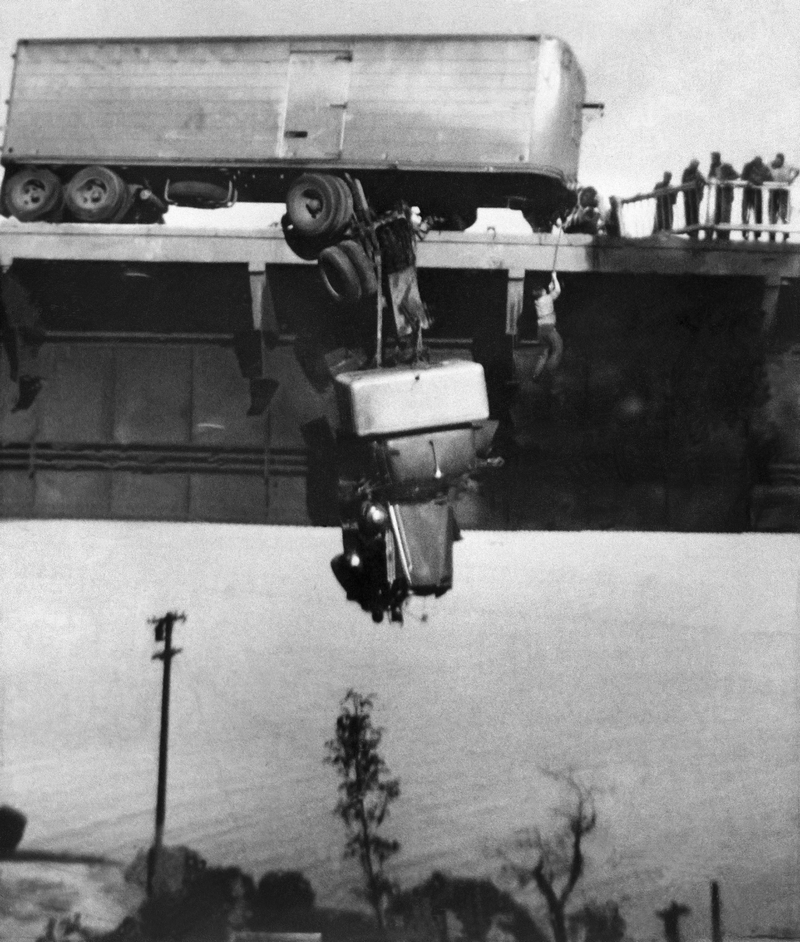 Paul Overby, one of two drivers trapped in the cab of a tractor trailer, is pulled to safety by a rope on the Pit River Bridge across Shasta Lake near Redding, Calif., May 3, 1953. Both Overby and co-driver Hank Baum were rescued before the cab burned and fell to the rocks below. Virginia Schau, an amateur photographer, used a Kodak Brownie camera to shoot the photo. (Virginia Schau via AP)