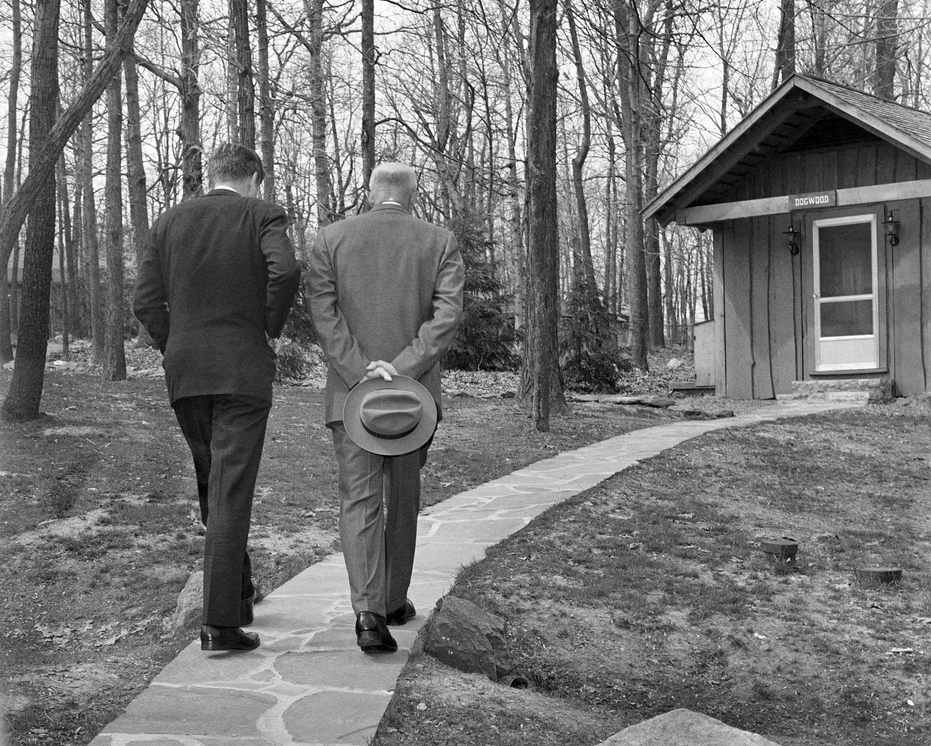 With their heads bowed, President John F. Kennedy, left, walks along a path at Camp David near Thurmont, Md., with former President Dwight D. Eisenhower, April 22, 1961, as the two met to discuss the Bay of Pigs invasion. The photo was shot between the legs of a Secret Service agent. (AP Photo/Paul Vathis)