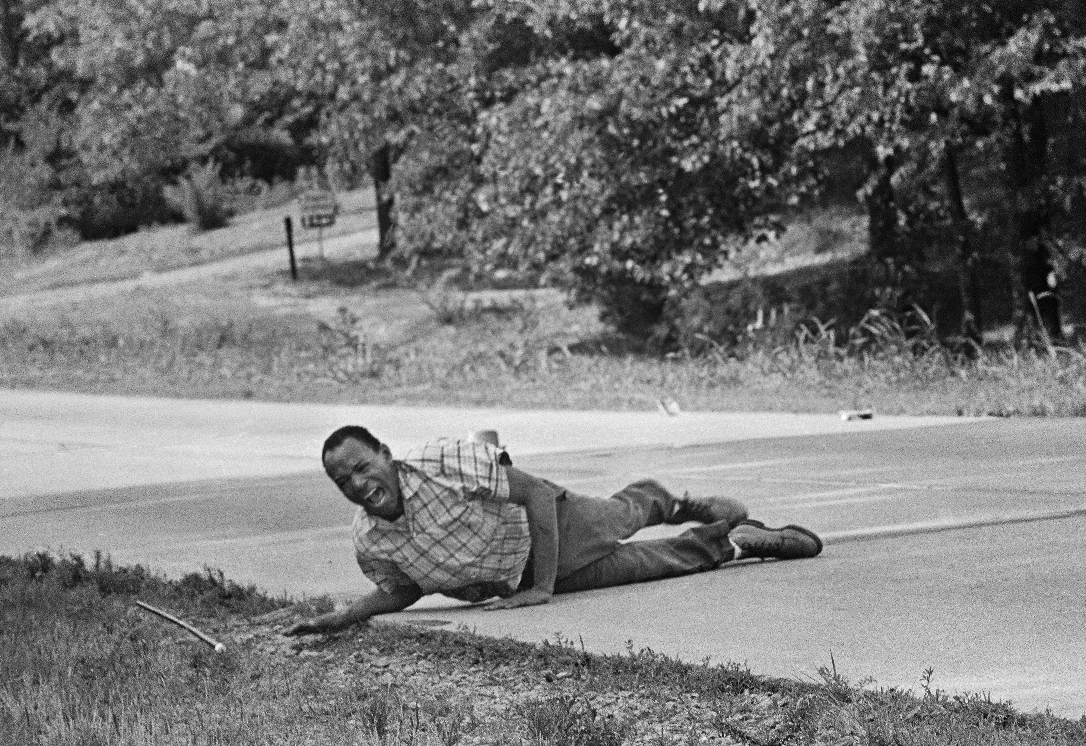 Civil rights activist James Meredith grimaces in pain as he pulls himself across Highway 51 after being shot in Hernando, Miss., June 6, 1966. Meredith was leading the March Against Fear to encourage African Americans to exercise their voting rights when he was shot. He completed the march from Memphis, Tenn., to Jackson, Miss., after treatment of his wounds. (AP Photo/Jack Thornell)