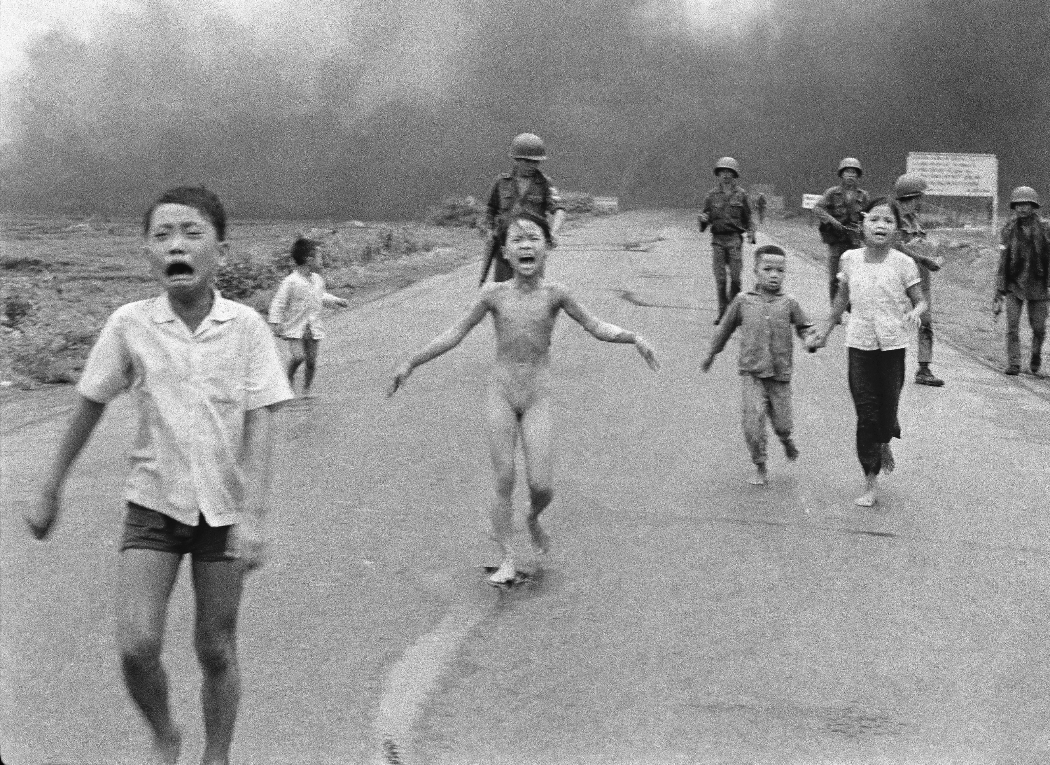South Vietnamese forces follow after terrified children, including 9-year-old Kim Phuc, center, as they run down Route 1 near Trang Bang after an aerial napalm attack against suspected Viet Cong hiding places on June 8, 1972. Kim Phuc had ripped off her burning clothes after a South Vietnamese plane mistakenly dropped its incendiary bombs on South Vietnamese troops and civilians. The young girl is accompanied by her injured brothers and cousins; behind them are Vietnamese soldiers of the 25th Division. (AP Photo/Nick Ut)