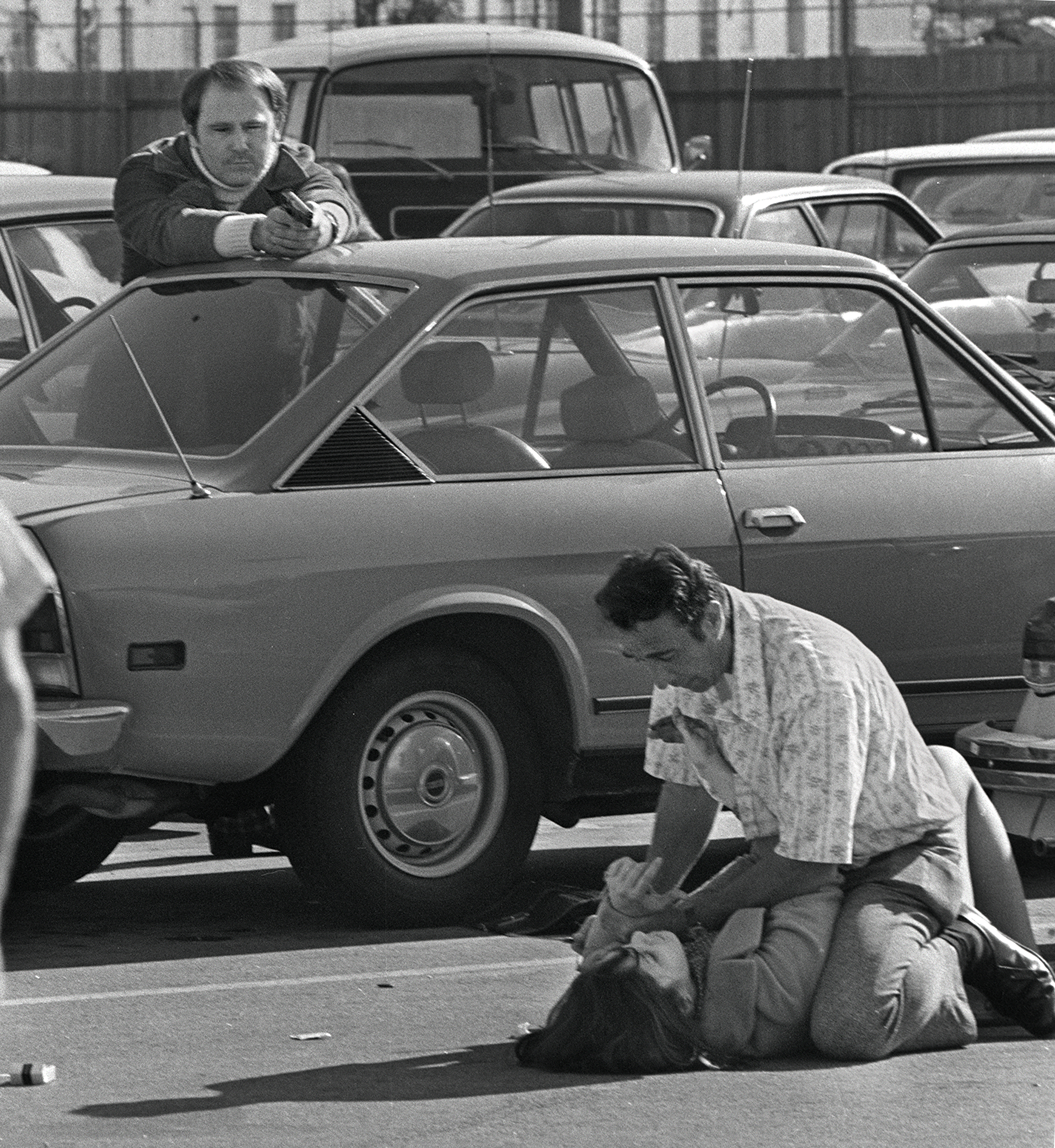 George H. Derby, left, a security guard, aims his gun at Edward F. Fisher, 39, who holds a knife to the throat of Ellen Sheldon, 22, during a kidnapping attempt in a Hollywood parking lot, Nov. 23, 1973. Sheldon managed to struggle to her feet, and seconds later Derby fired once after warning the suspect repeatedly. Fisher was killed instantly; Sheldon sustained minor injuries. (Anthony K. Roberts via AP)