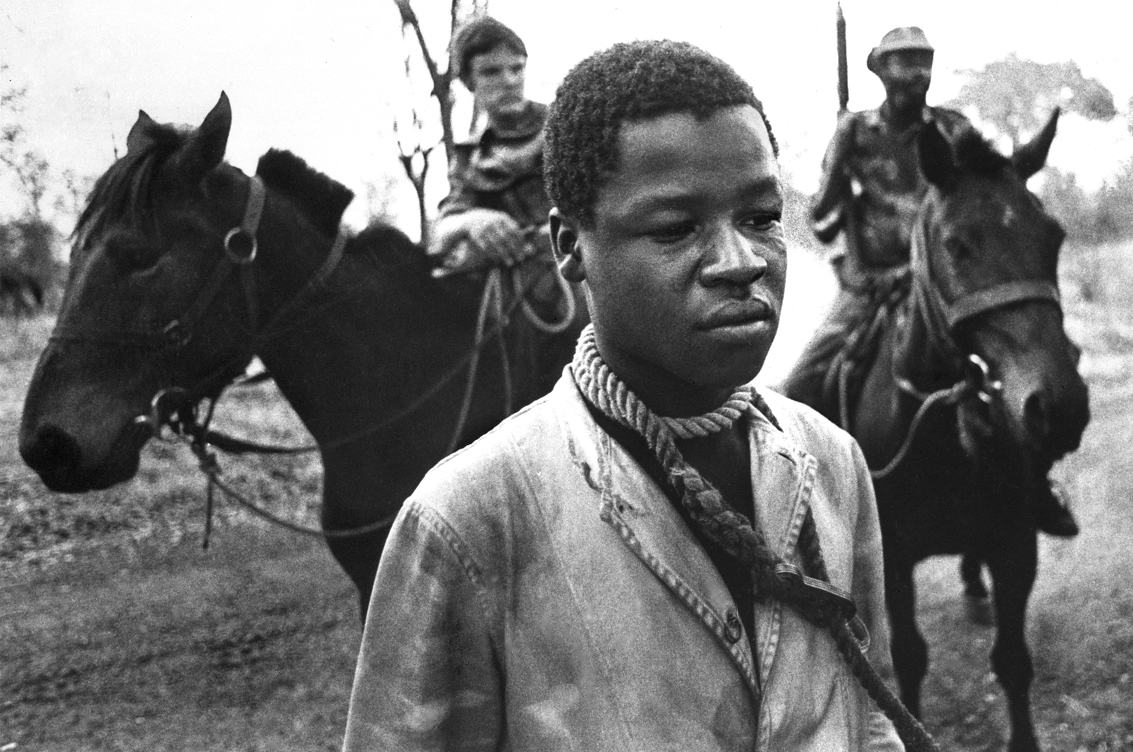 A Rhodesian prisoner stands with a rope tied around his neck to prevent escape, placed there by Rhodesian cavalrymen, background, who detained him for questioning in Lupane, southern Rhodesia, in September 1977. Rhodesia's white-dominated government was countering black guerrilla activities with militant armed forces. (AP Photo/J. Ross Baughman)
