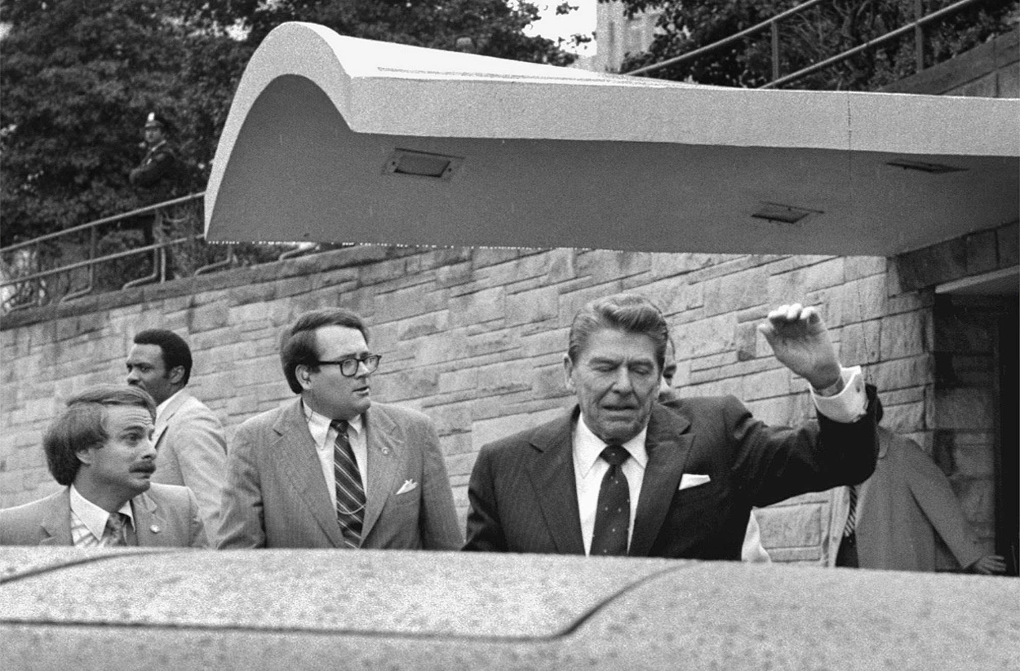 U.S. President Ronald Reagan looks to his left and holds up his left arm as a secret service agent places a hand on his shoulder and pushes the President into his limousine after he was shot leaving a Washington hotel, Monday, March 30, 1981. (AP Photo/Ron Edmonds)