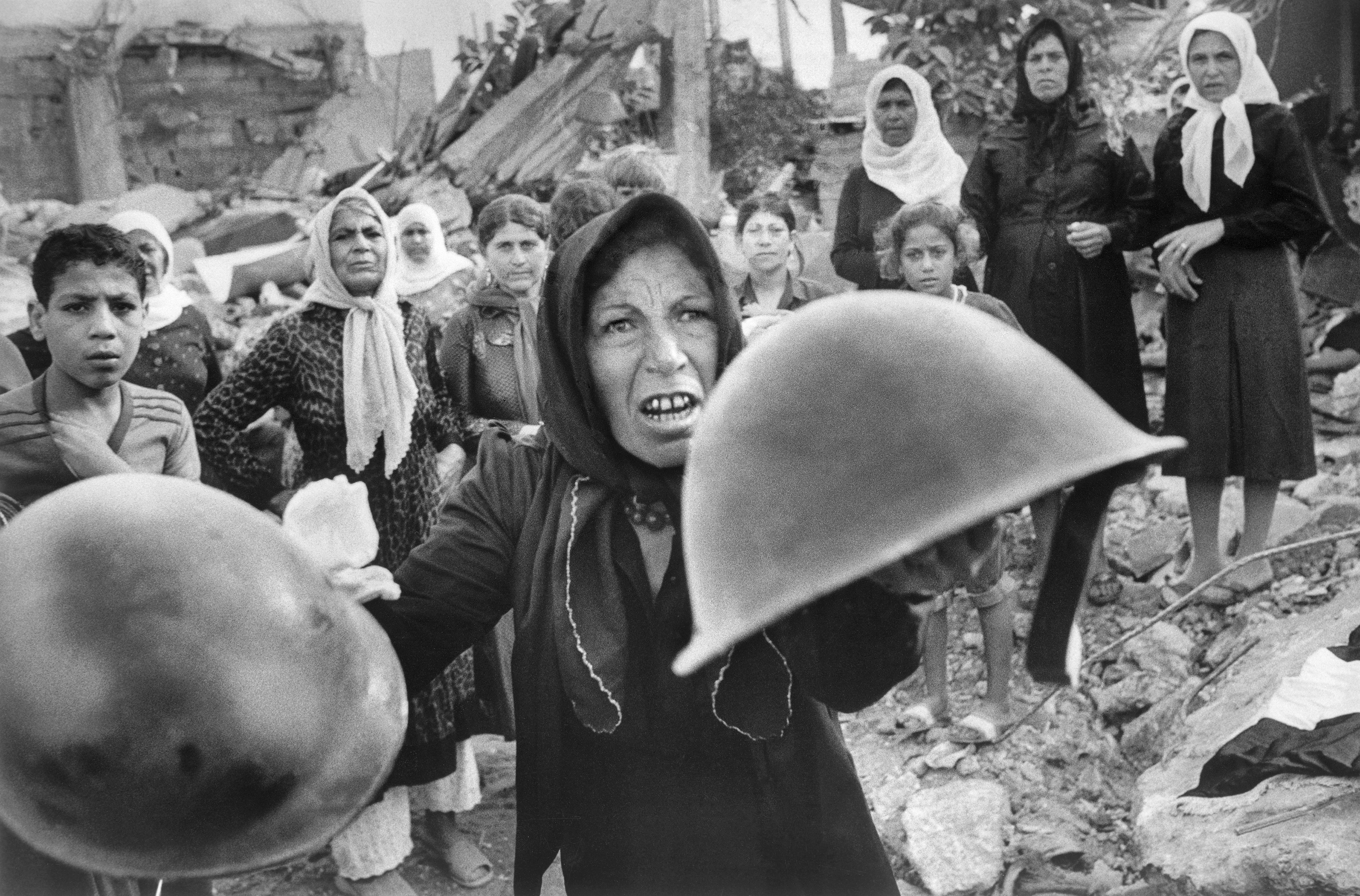 A Palestinian woman brandishes helmets during a memorial service in Beirut September 27, 1982, for victims of Lebanon's Sabra refugee camp massacre. She claimed the helmets ere worn by those who massacred hundreds of her countrymen. (AP Photo/Bill Foley)