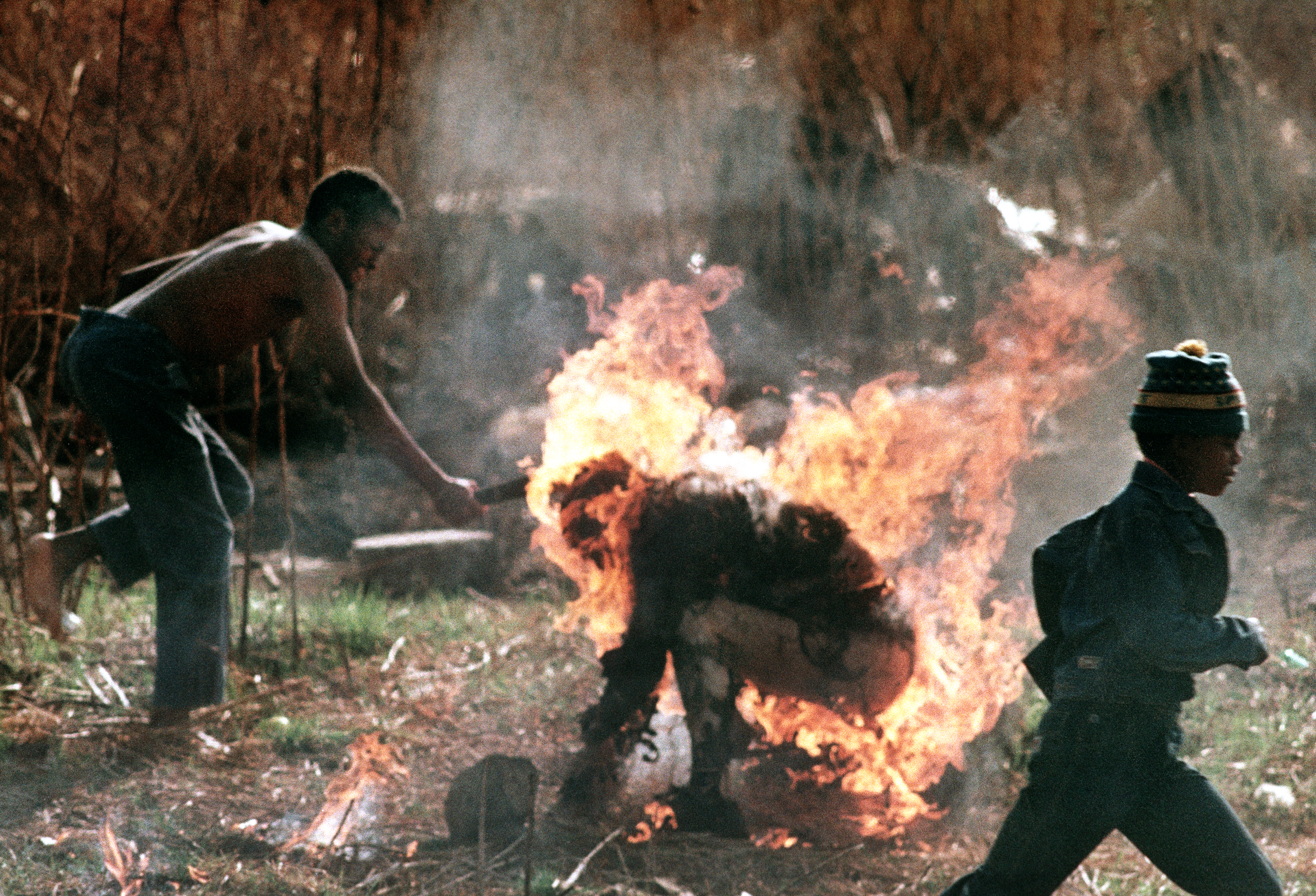 The burning body of a man identified as a Zulu Inkatha supporter is clubbed by a follower of the rival African National Congress during factional violence in Soweto, South Africa, on Sept. 15, 1990. (AP Photo/Greg Marinovich)