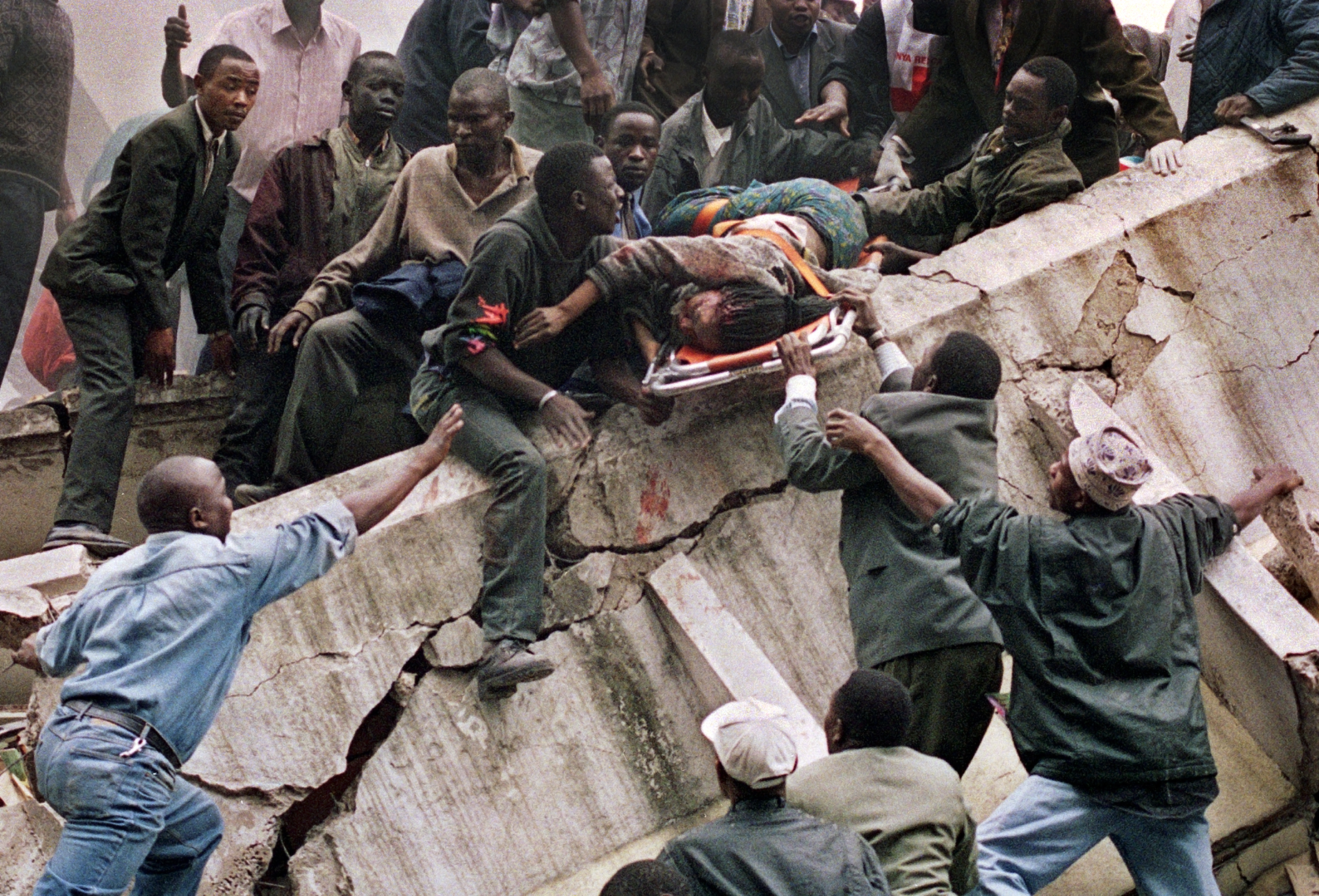 Rescue workers carry Susan Francisca Murianki, a U.S. Embassy office worker, from the rubble of a collapsed building in next to the embassy in Nairobi on Aug. 7, 1998 after terrorist bombs exploded minutes apart outside the U.S. embassies in the Kenyan and Tanzanian capitals. In Nairobi alone more than 200 people were killed and about 4,000 wounded. (AP Photo/Khalil Senosi)