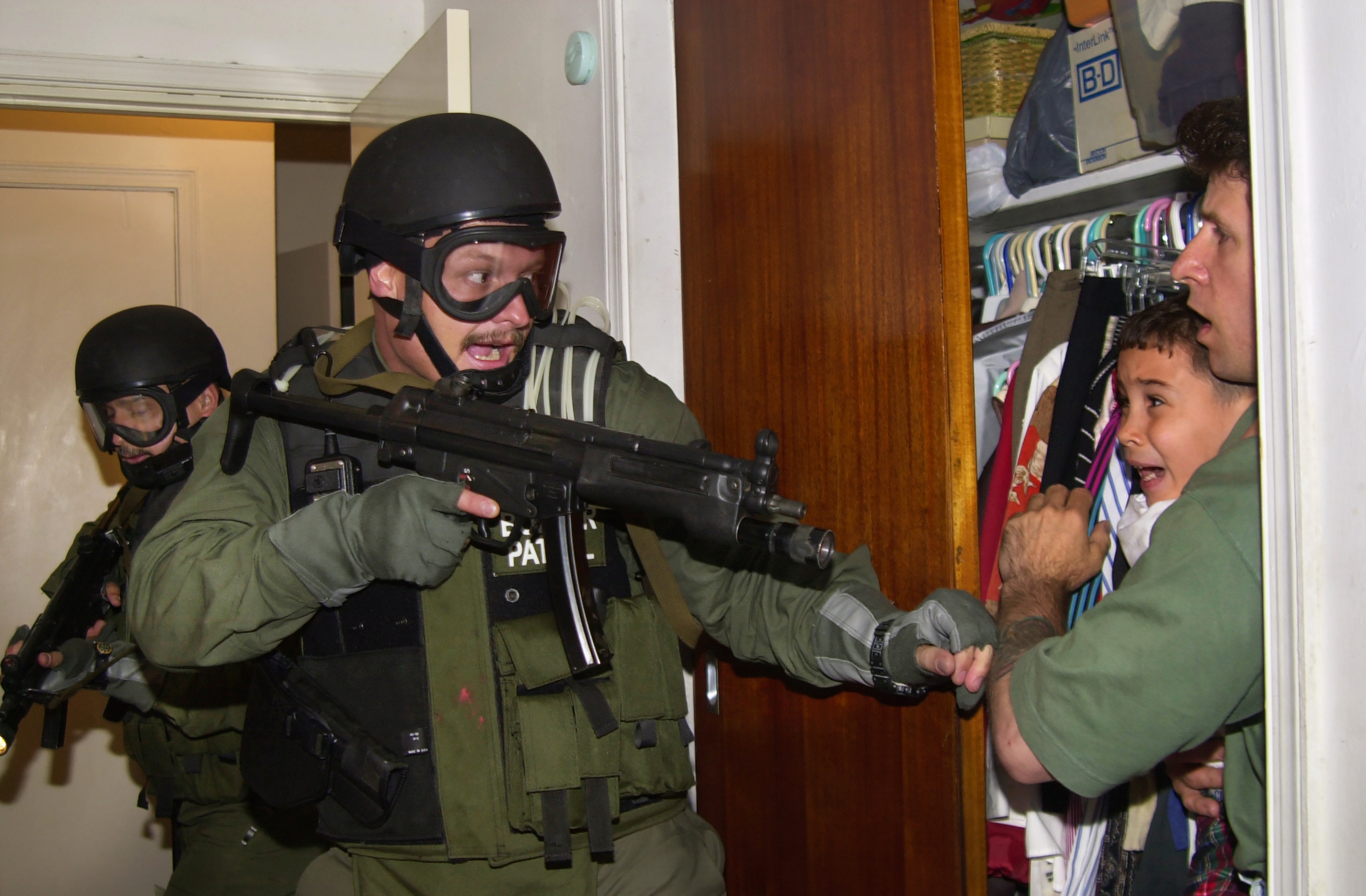 Armed federal agents enter the bedroom of a home in Miami's Little Havana on April 22, 2000, as 6-year-old Elian Gonzalez is held in a closet by Donato Dalrymple, one of the two men who rescued the boy from the ocean months earlier. The agents took custody of Elian at the home of his Miami relatives, eventually repatriating him to Cuba with his father. (AP Photo/Alan Diaz)