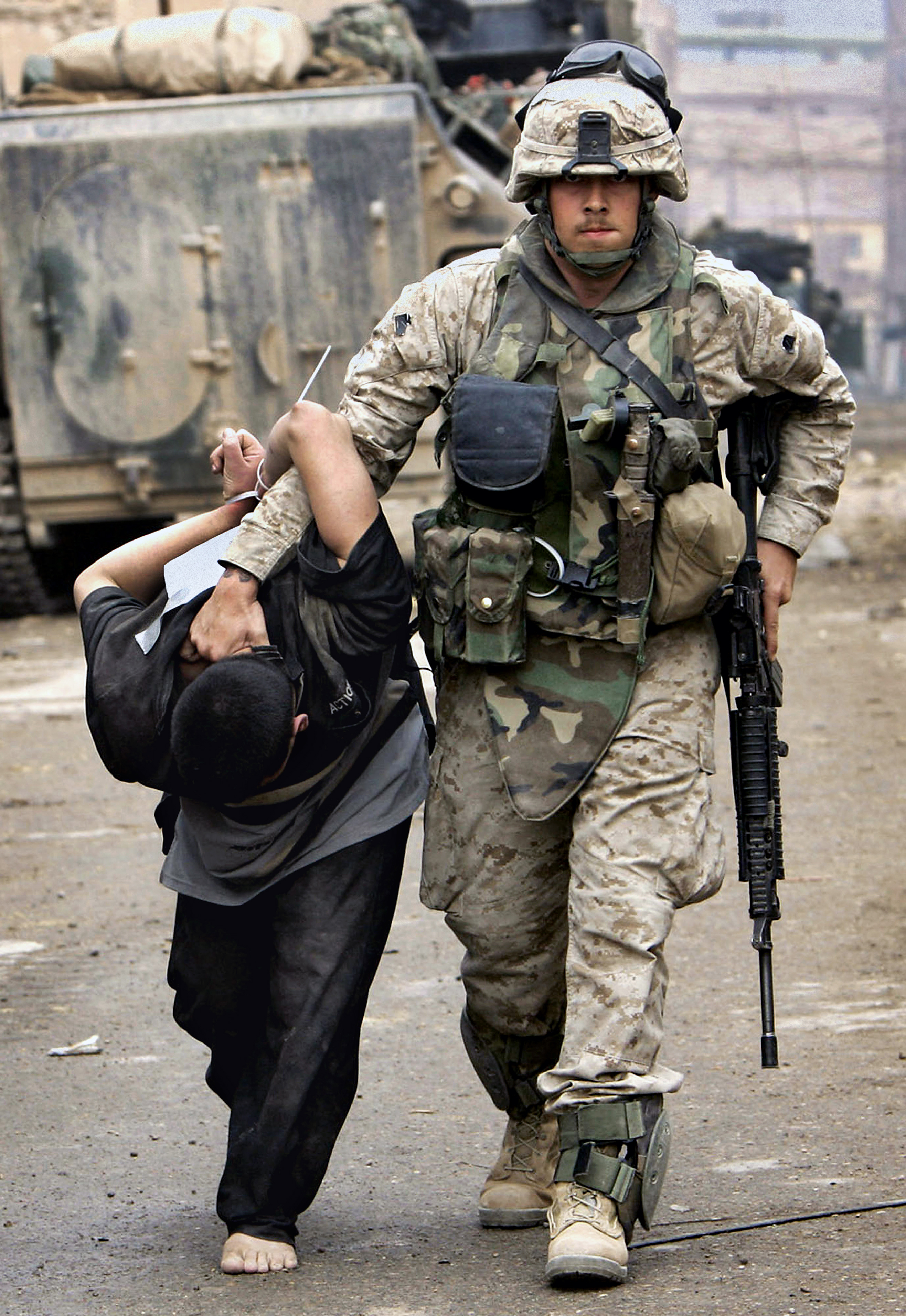 A U.S. Marine leads away a captured Iraqi man in the center of Fallujah, Iraq, Nov. 12, 2004. This photograph is one in a portfolio of twenty taken by eleven different Associated Press photographers throughout 2004 in Iraq. The Associated Press won a Pulitzer prize in breaking news photography, Monday April 4, 2005 for the series of pictures of bloody combat in Iraq. The award was the AP's 48th Pulitzer. (AP Photo/Anja Niedringhaus)