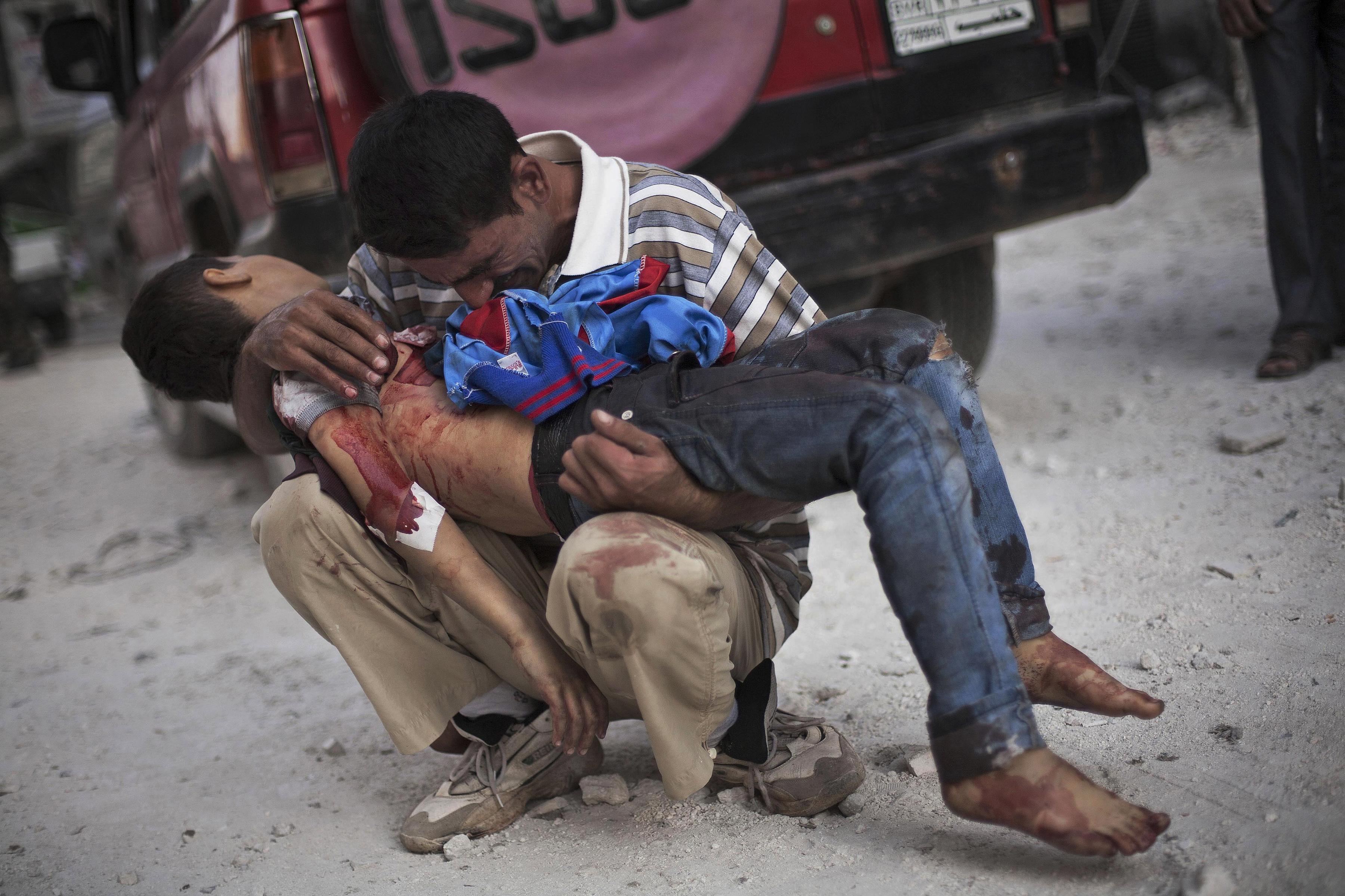 A Syrian man cries while holding the body of his son near Dar El Shifa hospital in Aleppo, Syria, Oct. 3, 2012. The boy was killed by the Syrian army. This image was one in a series of 20 by AP photographers that won the 2013 Pulitzer Prize in Breaking News Photography. (AP Photo/Manu Brabo)