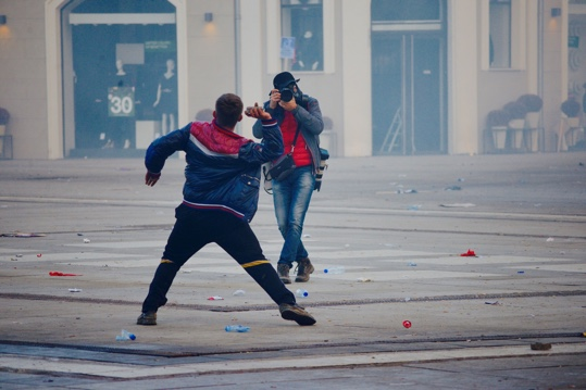 Photographer taking picture of rioter throwing an object