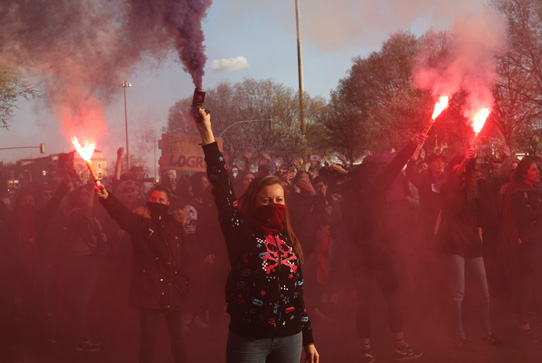 Women march holding flares in Madrid, Spain