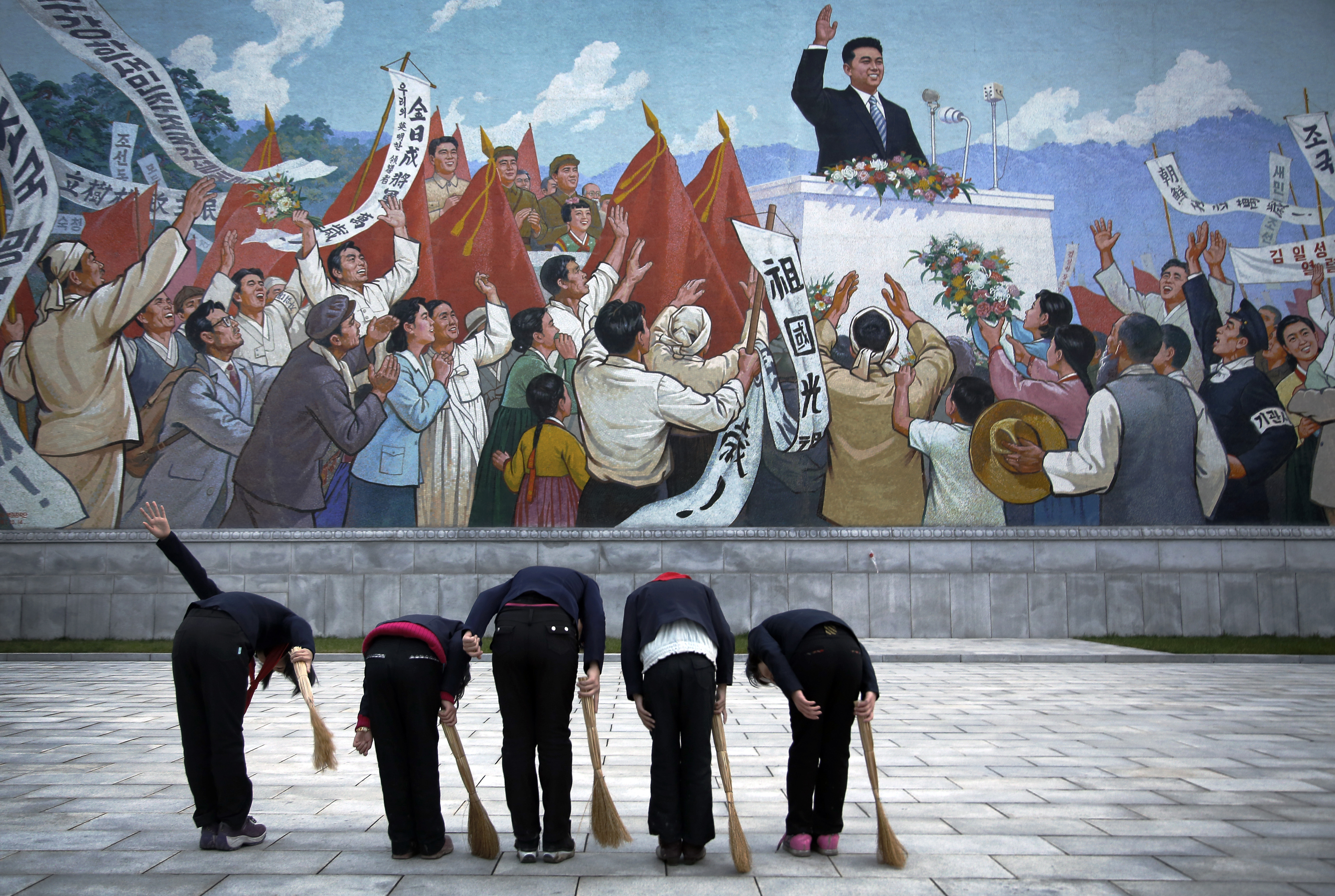 North Korean school girls holding brooms bow to pay their respects toward a mural which shows the late North Korean leader Kim Il Sung delivering a speech, before sweeping the area surrounding this mural on Tuesday, Dec. 1, 2015, in Pyongyang, North Korea, one of over 70 photos that will be on display at Objectifs in Singapore. (AP Photo/Wong Maye-E)
