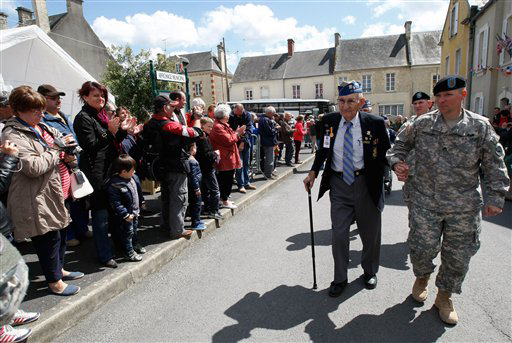 U.S. WW II veteran 89 year old Arden C. Earll, from Erie Pensylvania, who landed on Omaha Beach on June 6, 1944 with the 29th infantry division regiment, is applauded as he arrives at a ceremony in honor of the division, in La Cambe, France, as part of the commemoration of the 70th D-Day anniversary, Wednesday June 4, 2014. World leaders and veterans are preparing to mark the 70th anniversary of the invasion this week in Normandy. (AP Photo/Claude Paris)