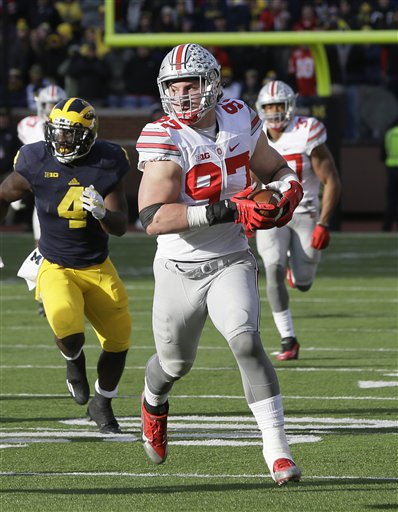 Ohio State defensive end Joey Bosa, who was on last year's AP All-America team and is a contender for 2015, runs from Michigan running back De'Veon Smith after intercepting a pass during the second half of an NCAA college football game, Saturday, Nov. 28, 2015, in Ann Arbor, Mich. (AP Photo/Carlos Osorio)