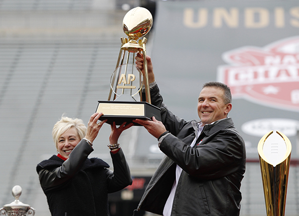 Ohio State coach Urban Meyer, right, and Eva Parziale, east regional director for The Associated Press, hold up the AP college football championship trophy as the Buckeyes were the unanimous No. 1 selection in the final AP Top 25 of the 2014 season. The trophy was presented at a national championship celebration at Ohio Stadium in Columbus, Ohio, Saturday, Jan. 24, 2015. (AP Photo/Paul Vernon)