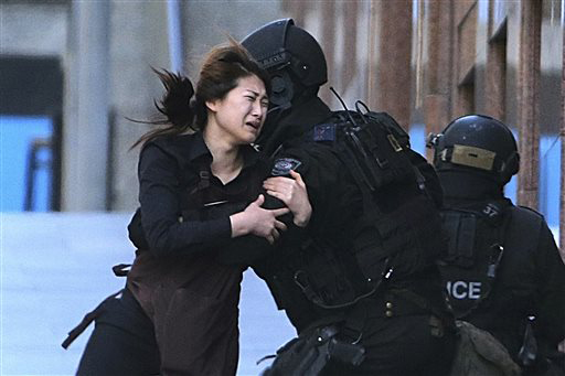 In this Dec. 15, 2014, file photo, Jieun Bae runs to armed tactical response police officers for safety after she escaped from a cafe under siege at Martin Place in the central business district of Sydney, Australia. Rob Griffith, the Sydney-based Associated Press photographer, won the 2015 News Photography award Thursday, Dec. 3, 2015 by the Walkley Foundation for his coverage of the hostage crisis at the Sydney cafe in December 2014. (AP Photo/Rob Griffith, File)