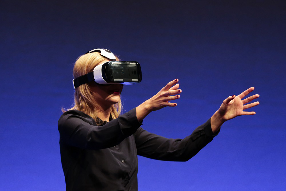 In this Sept. 3, 2014 file photo, British television presenter Rachel Riley shows a virtual-reality headset called Samsung Gear VR of the consumer electronic fair IFA in Berlin. (AP Photo/Markus Schreiber)