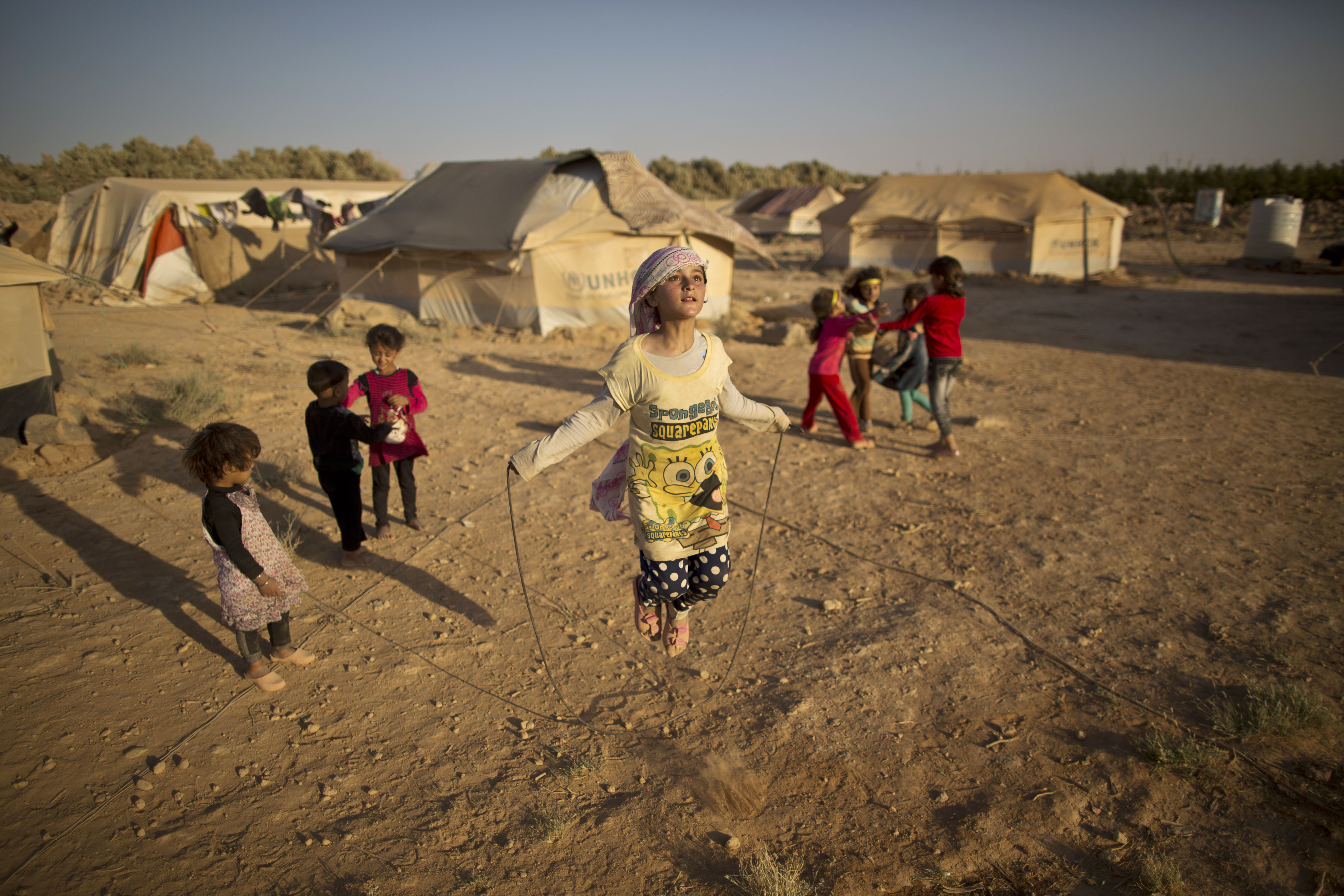 A Syrian girl skips a rope while she and other children play near their tents at an informal tented settlement near the Syrian border on the outskirts of Mafraq, Jordan, July 19, 2015. This is one of the images that will be on display at Xposure International Photography Festival. (AP Photo/Muhammed Muheisen)