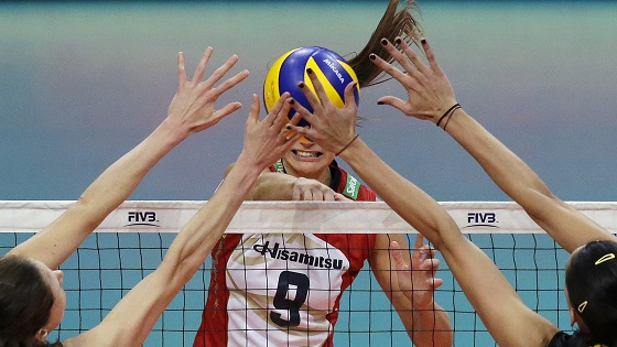 Female volleyball players blocking ball being hit over a net