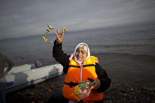 Elderly refugee throws candy in the air