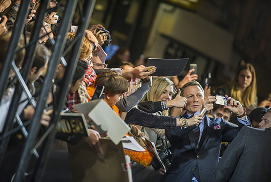 Crowd reaching over barricade to take selfies with Daniel Craig