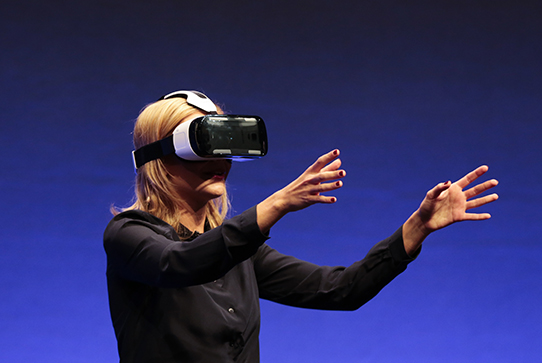 Woman wearing virtual reality headset on stage