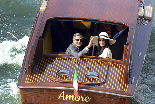 George Clooney and Amal Alamuddin waving from water taxi