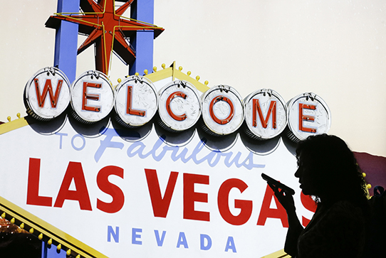 Silhouette of woman in front of Las Vegas sign