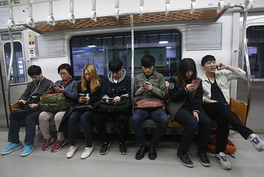 People looking at phones on subway
