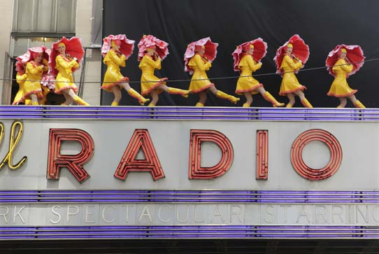 The Rockettes standing on top of the Radio City Music Hall sign