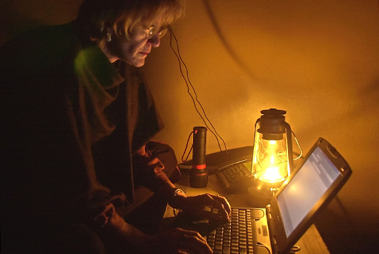 Journalist working on a computer by the light of a lantern