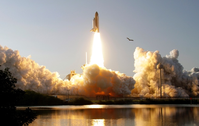 Space shuttle launching over water