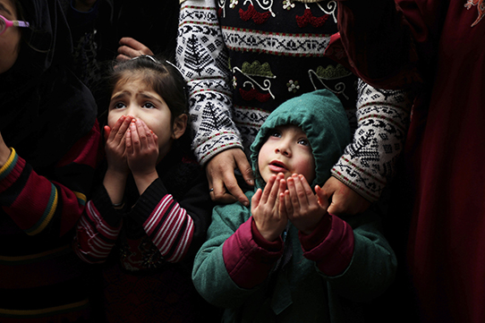 Kashmiri Muslim children pray as a priest displays a relic of Sufi saint Sheikh Syed Abdul Qadir Jeelani outside his shrine in Srinagar, Indian controlled Kashmir, Monday, Dec. 9, 2019. Devotees gathered at the shrine for the 11-day festival that marks the death anniversary of the Sufi saint. (AP Photo/Mukhtar Khan)