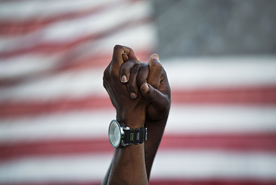 Hands joined in front of American flag