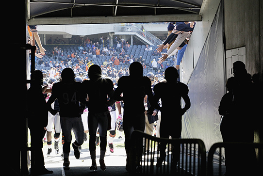 Silhouettes of football players jogging into the locker room